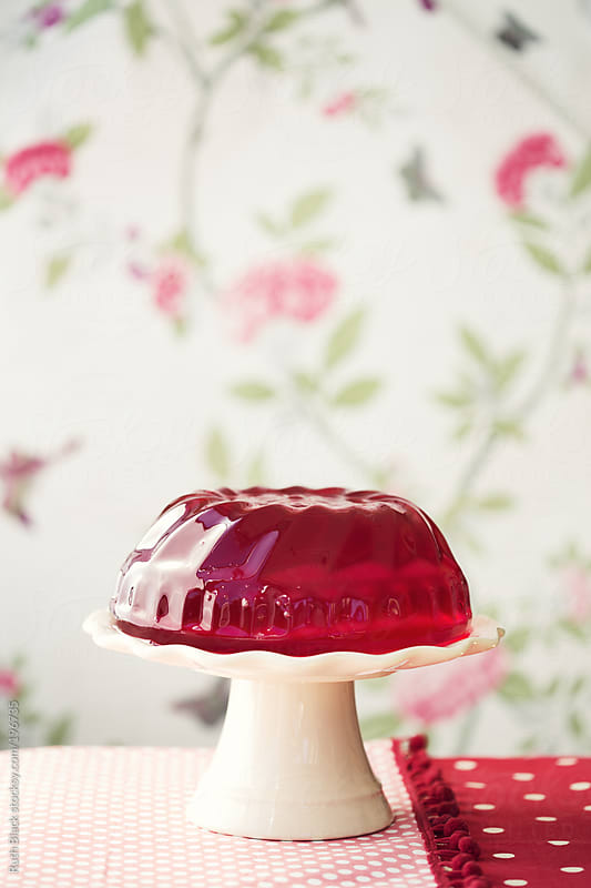 Red jello on a cakestand by Ruth Black for Stocksy United