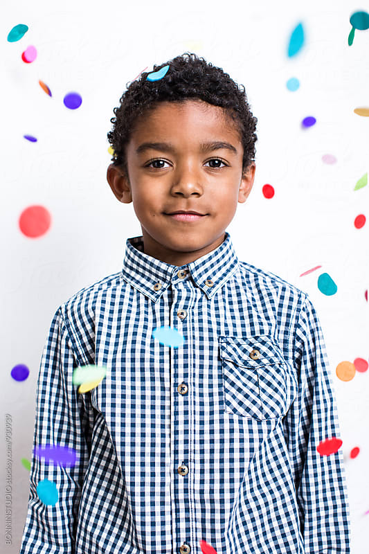 Portrait of a little boy as confetti falls from above. by BONNINSTUDIO for Stocksy United