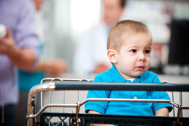 Pharmacy: Boy Being Ignored in Shopping Cart by Sean Locke for Stocksy United