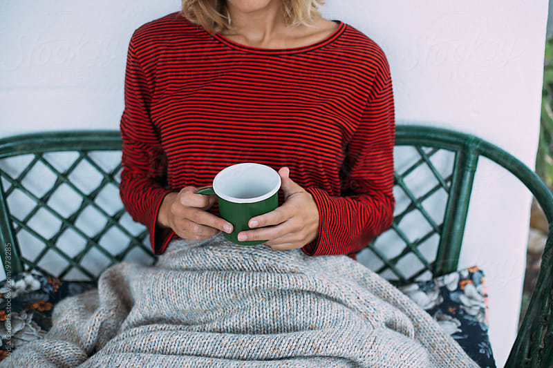 Woman holding a cup of coffee with a blanket  by Lydia Cazorla for Stocksy United