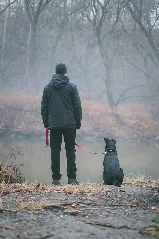 A man and his dog stand by the waterside on a foggy winter day by Kathryn Swayze for Stocksy United
