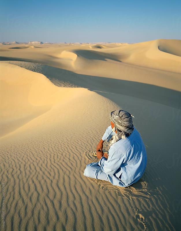 Arab sitting in sand dunes of the Sahara. Egypt. by Hugh Sitton for Stocksy United