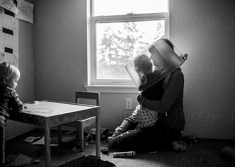 Mother and daughter Play Hide and seek under a Plastic Tub by Amanda Voelker for Stocksy United