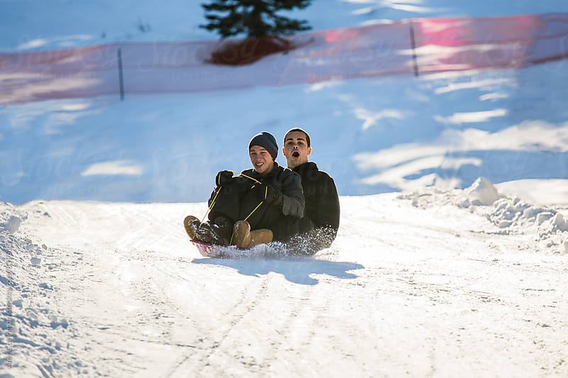 Two young men riding a sled downhill by Amy Covington for Stocksy United