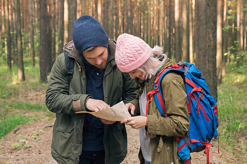 Couple of backpackers using map in forest by Danil Nevsky for Stocksy United
