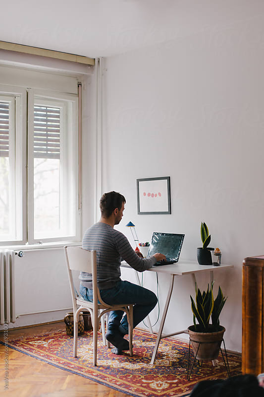 Man working on a laptop in his room by Marija Mandic for Stocksy United