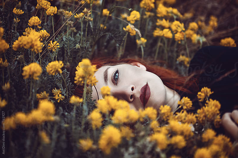 Red Haired Woman laying in flowers  by Ani Dimi for Stocksy United