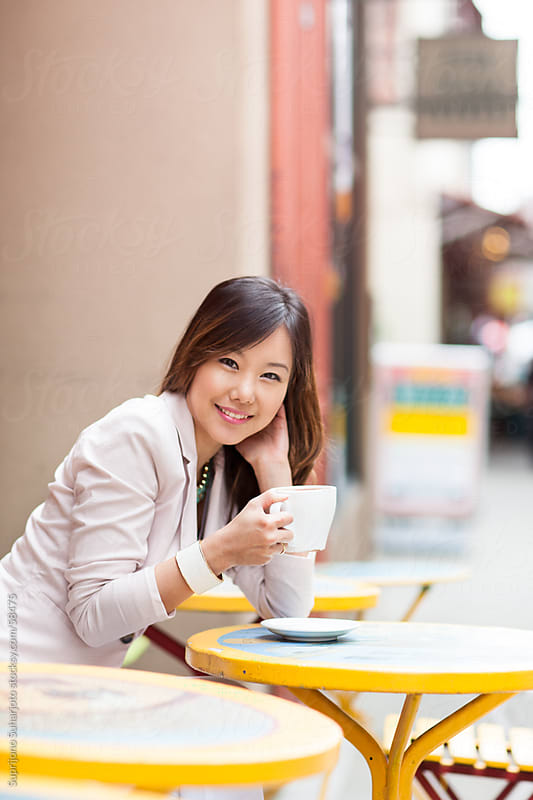 Beautiful Asian woman holding a cup of coffee at an outdoor cafe by Suprijono Suharjoto for Stocksy United
