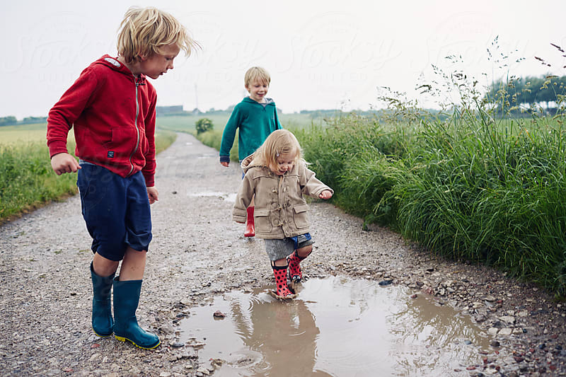 Three children out walking on a rainy day by sally anscombe for Stocksy United