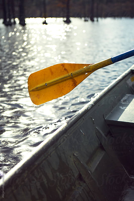 Yellow paddle hanging off a boat by Alicja Colon for Stocksy United