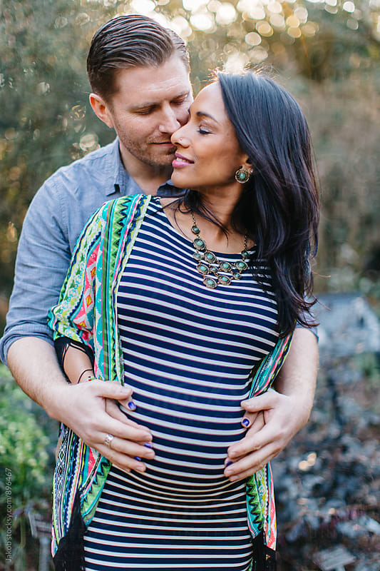 A beautiful pregnant woman being embracing by her husband by Jakob for Stocksy United