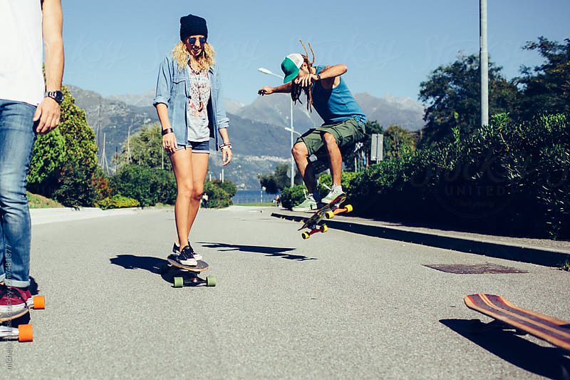 Friends having fun with skateboard outdoors by michela ravasio for Stocksy United