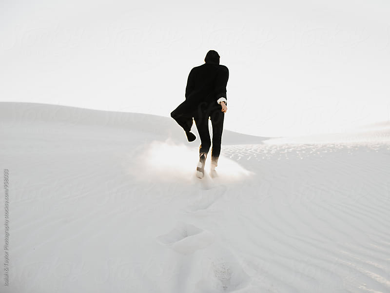 Woman running up a sand dune by Isaiah & Taylor Photography for Stocksy United