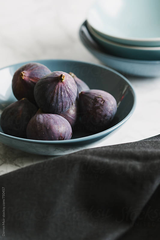 Ripe figs in a blue bowl on a table. by Darren Muir for Stocksy United