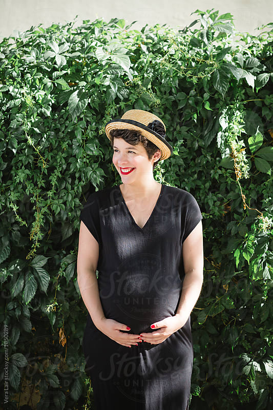 Portrait of a smiling pregnant woman by Vera Lair for Stocksy United