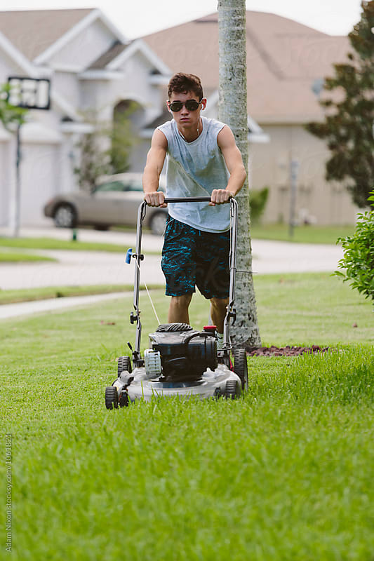 Teenage boy mowing the lawn by Adam Nixon for Stocksy United