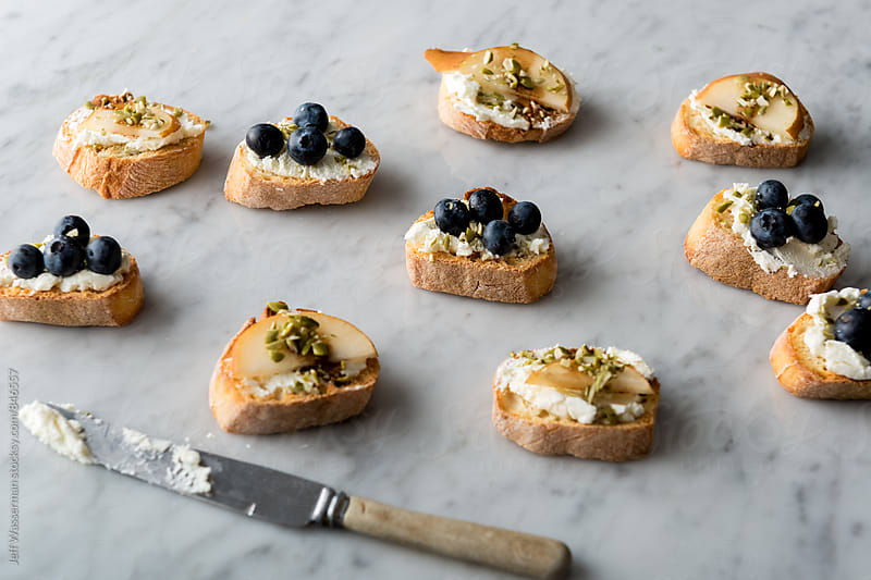 Crostini with Goats Cheese, Pear and Blueberry on Marble by Jeff Wasserman for Stocksy United