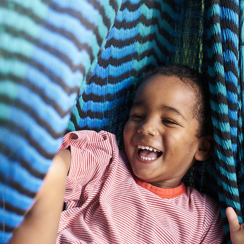 Boy laughing in a hammock by Per Swantesson for Stocksy United