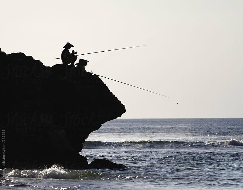Silhouette of fisherman fishing from a rock. by Koen Meershoek for Stocksy United