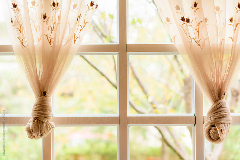 Tied muslin curtain in front of window with bright view by Lawren Lu for Stocksy United