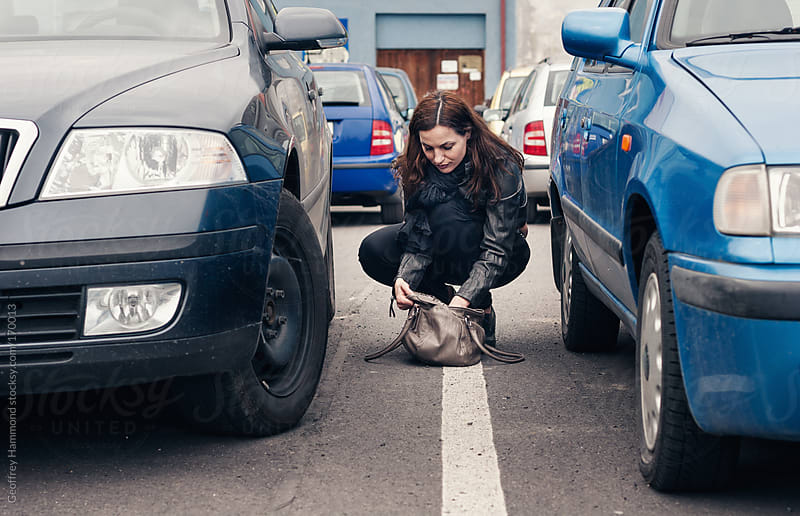Woman Between Cars Searching Purse for Keys  by Geoffrey Hammond for Stocksy United