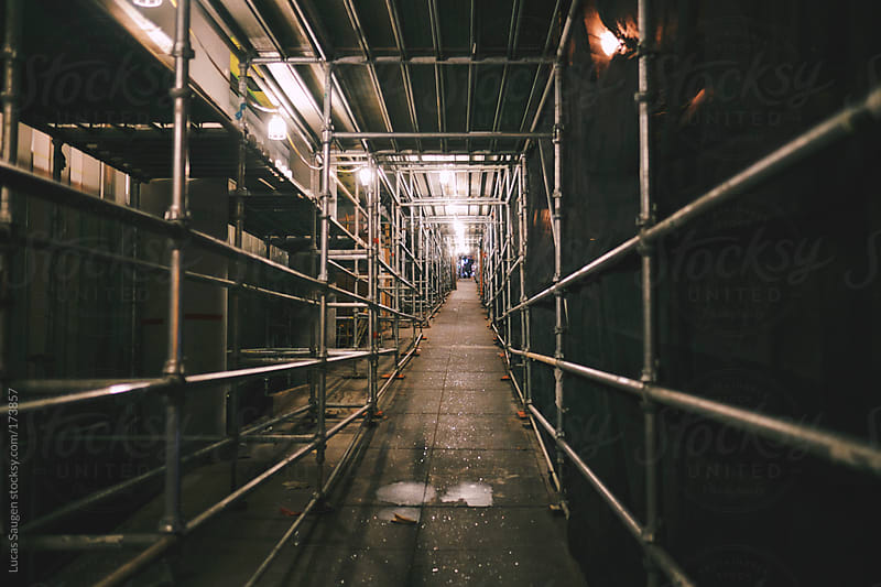 Scaffolding covering a sidewalk by a construction site by Lucas Saugen for Stocksy United