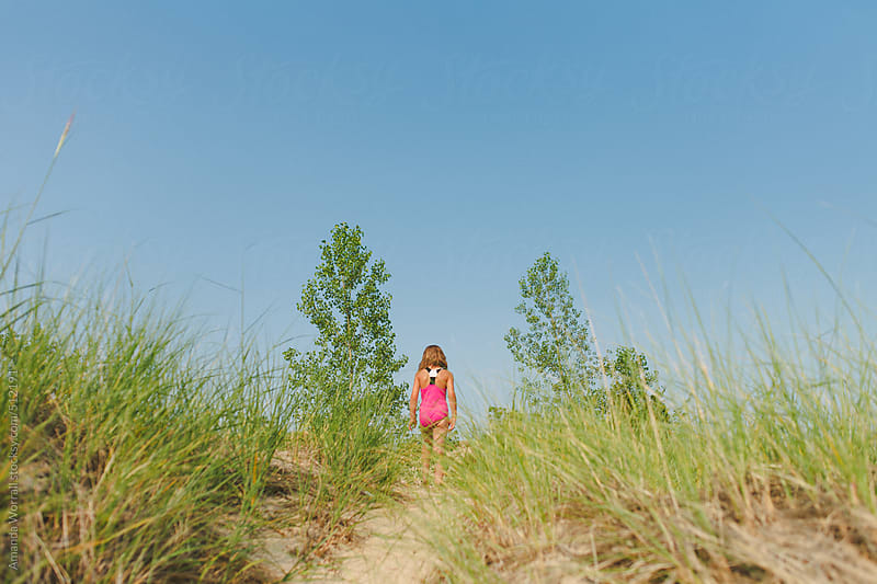 Girl wearing pink bathing suit walks up a sand dune by Amanda Worrall for Stocksy United