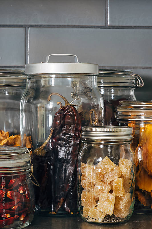 Jars of dried fruits and peppers sitting on a shelf. by Lucas Saugen for Stocksy United