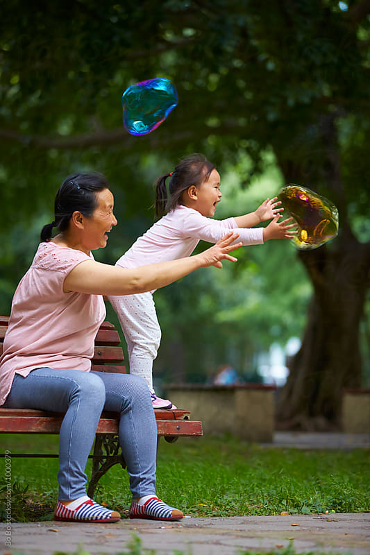 happy little asian girl  having fun with her grandmother by Bo Bo for Stocksy United