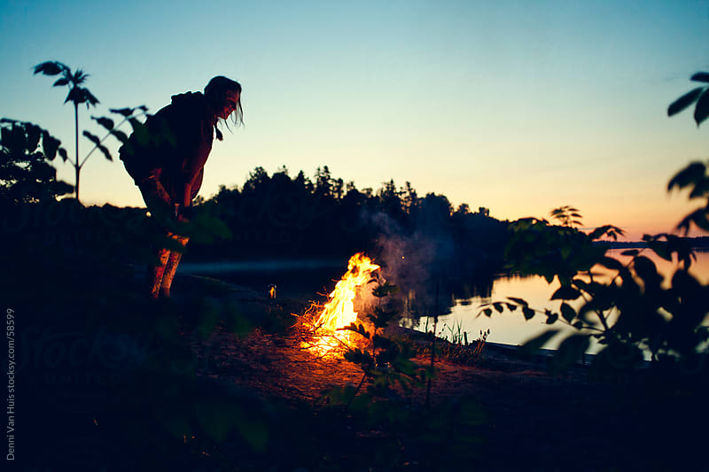 Young woman making a campfire right next to a lake by Denni Van Huis for Stocksy United