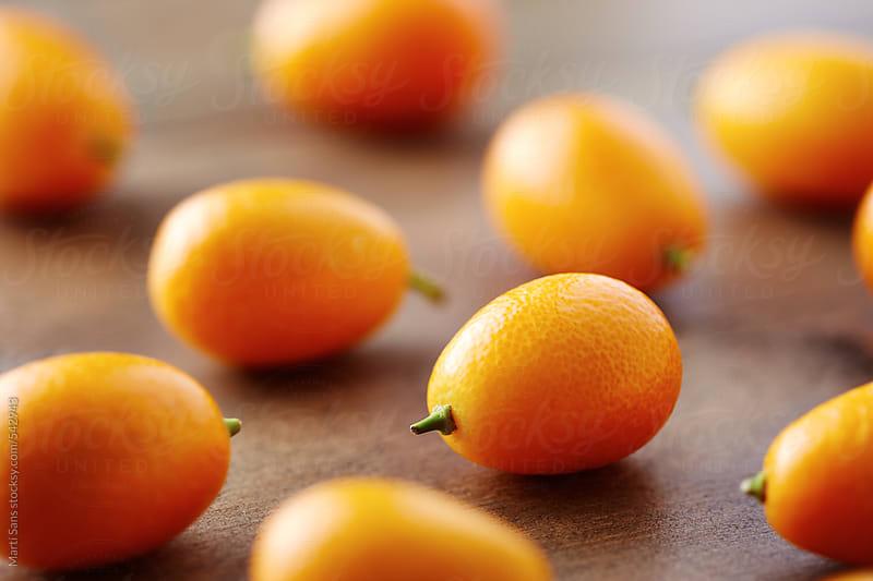 Kumquats on wooden background by Martí Sans for Stocksy United