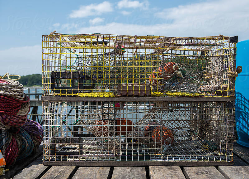 Lobster traps stacked on a dock on the coast of Maine by Cara Slifka for Stocksy United