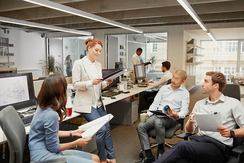 Business team looking at redhead leaning against desk by Aila Images for Stocksy United