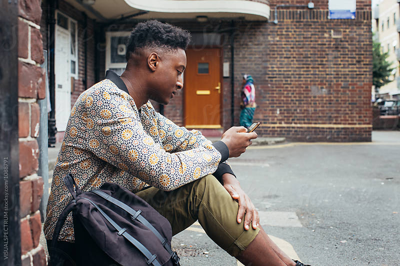 Profile of Young Fashionable Black Man Using Smartphone in Front of London Apartment Block by Julien L. Balmer for Stocksy United
