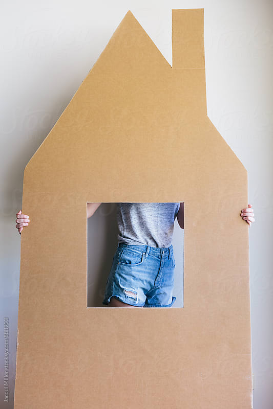 Unrecognisable female lifting a large cardboard cut out of a house by Jacqui Miller for Stocksy United