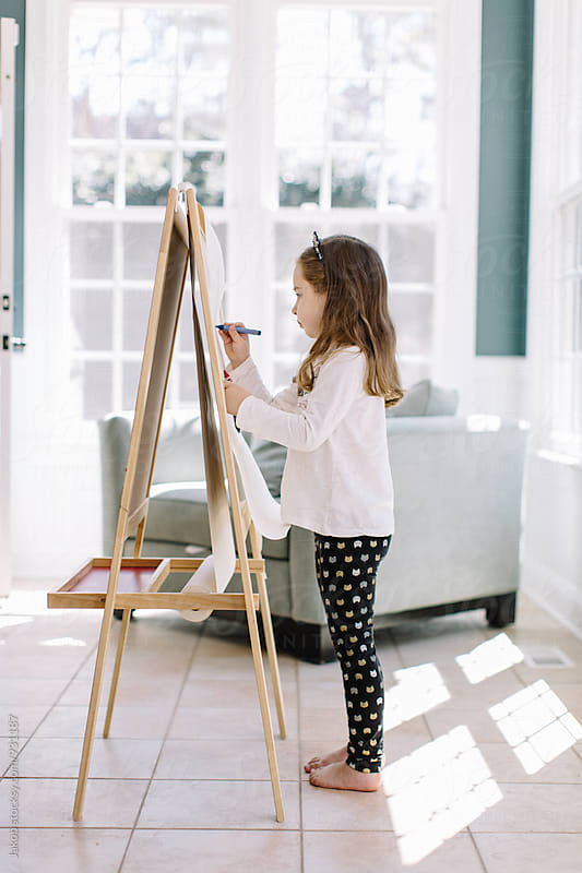 Cute young girl painting using an easel stand by Jakob for Stocksy United