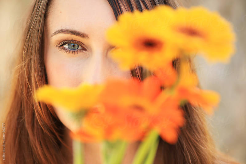 Portrait of a beautiful young woman with yellow flowers by rolfo for Stocksy United