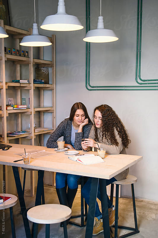 Young women sitting in cafe and using mobile phone by Danil Nevsky for Stocksy United