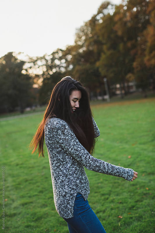 Beautiful young asian woman smiling outside on field at sunset in fall by Rob and Julia Campbell for Stocksy United