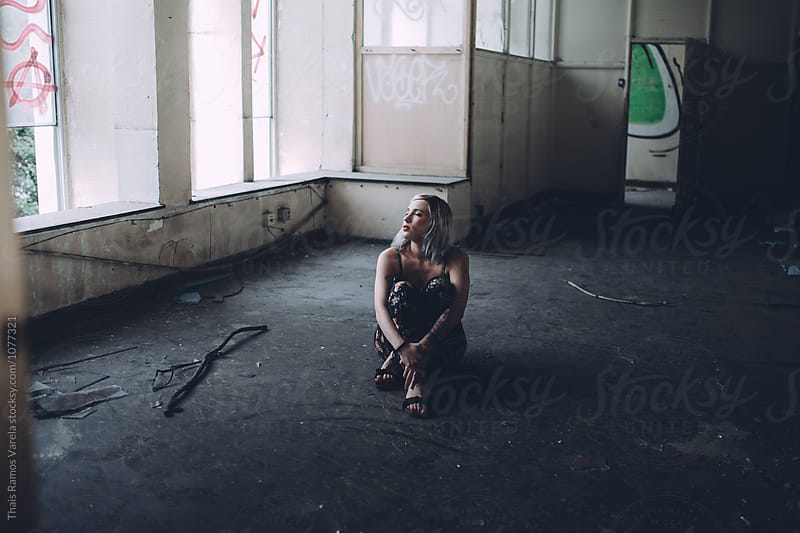 woman sitting in an empty room by Thais Ramos Varela for Stocksy United