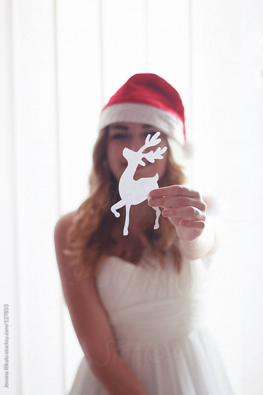 Girl holding Christmas pattern in her hand by Jovana Rikalo for Stocksy United