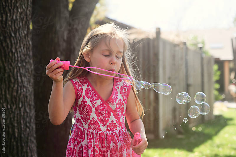 Young Girl Blows Bubbles in Pink Dress by Leigh Love for Stocksy United