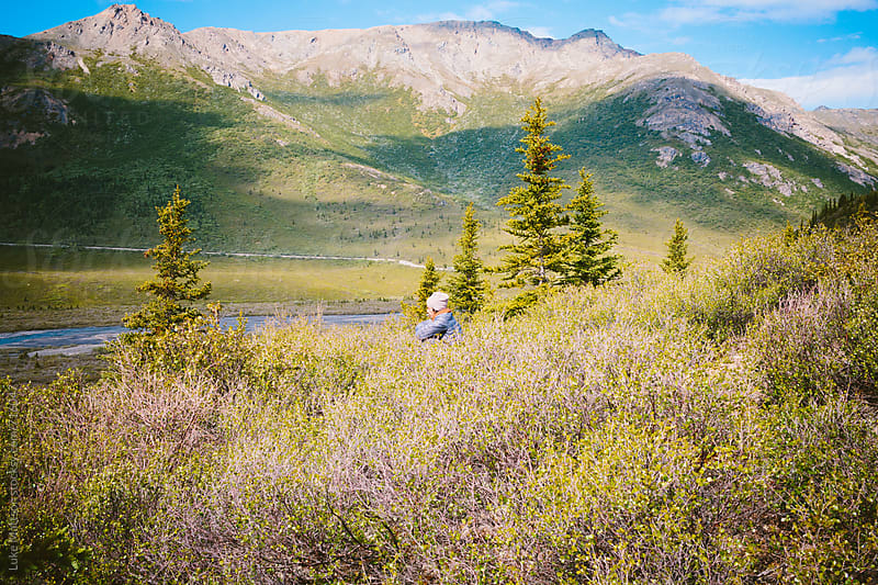Young Man Sits In The Brush On Top Of  A Hill Surrounded By Mountains by Luke Mattson for Stocksy United