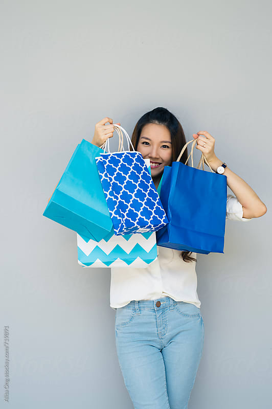 Smiling woman holding shopping bags by Alita Ong for Stocksy United