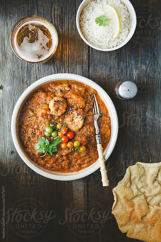 Prawn Curry with tomato garam masala yoghurt gravy served with basmati rice and poppadoms by Nadine Greeff for Stocksy United