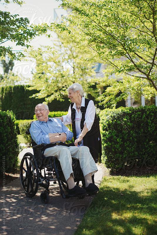 Happy, fun loving elderly couple outside in garden using wheelch