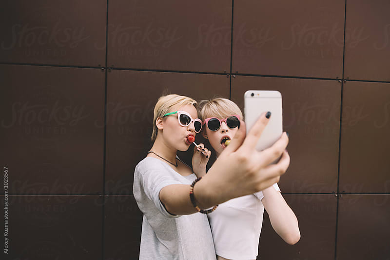 girlfriends with candy taking a selfie by Alexey Kuzma for Stocksy United