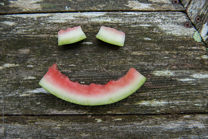 Watermelon rinds make a smiley face on a picnic table by Cara Dolan for Stocksy United