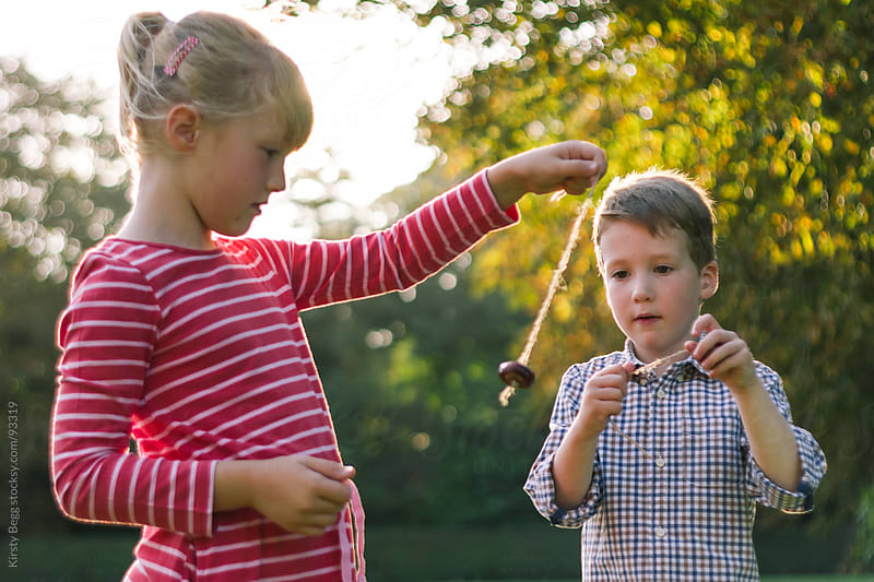 Boy and Girl playing conkers by Kirsty Begg for Stocksy United