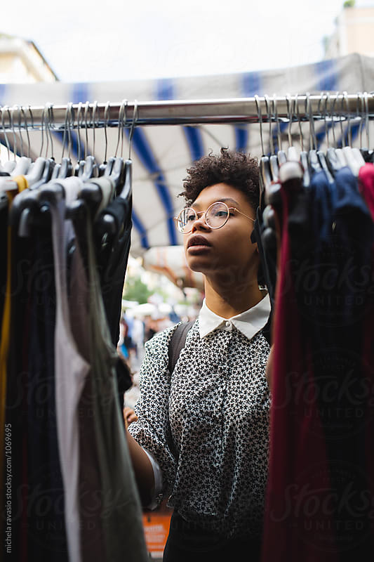 Beautiful woman browsing through dresses by michela ravasio for Stocksy United